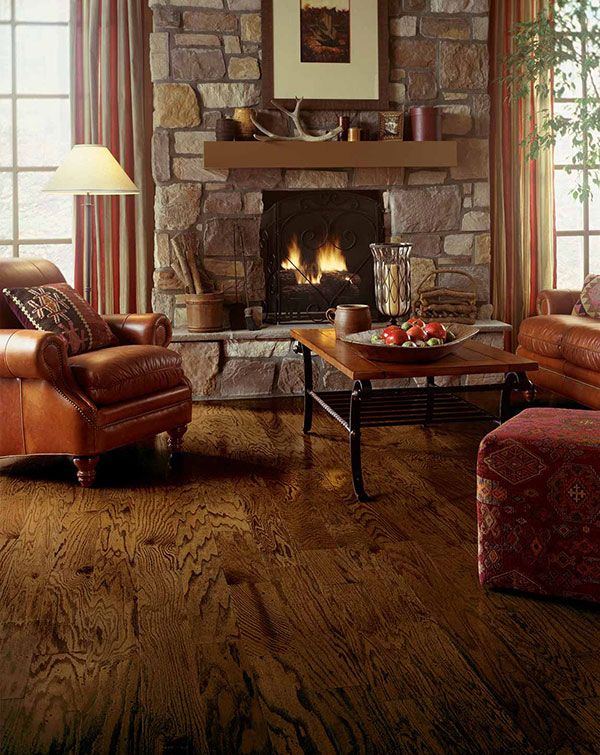 Family room with lit stone fireplace, hardwood floors, and overstuffed leather furniture that provides a woodsy theme.