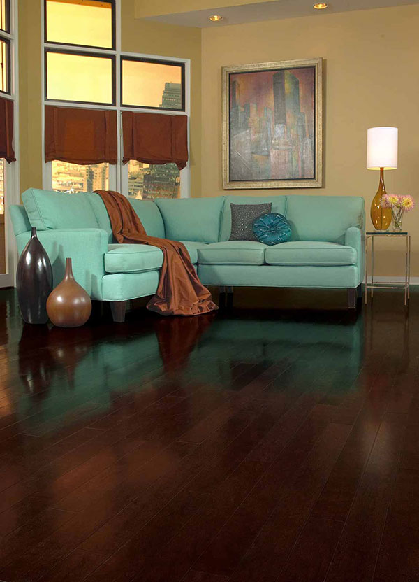 Teal pastel colored couch on dark brown wood floor