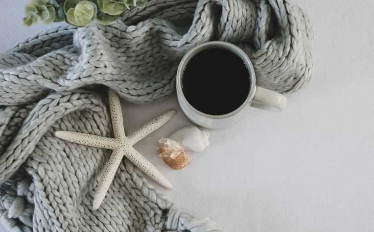 hygge with a scarf, coffee and sea shells