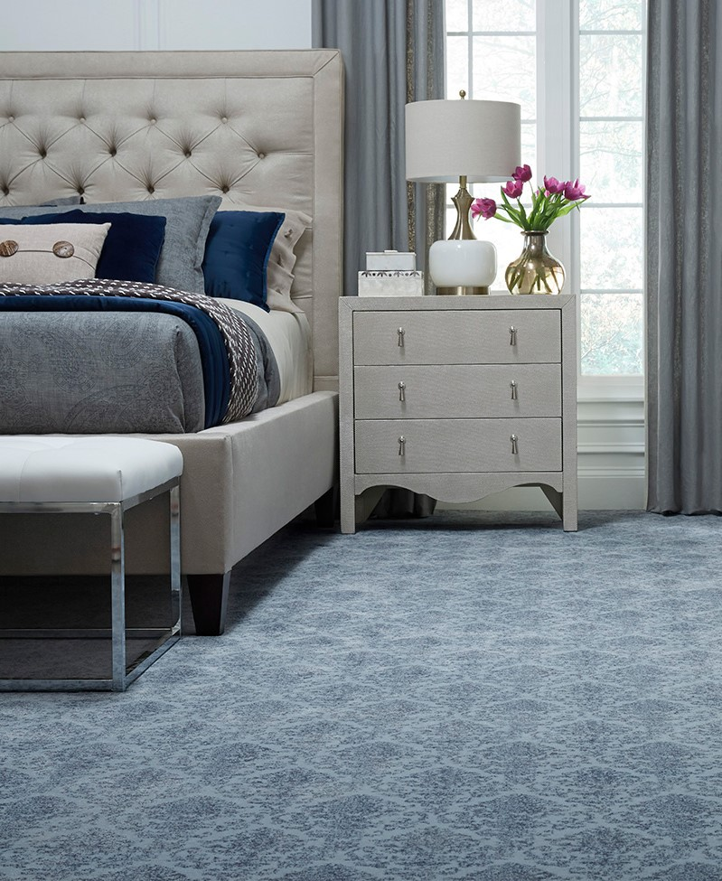 master bedroom and sidetable with blue pattern carpet